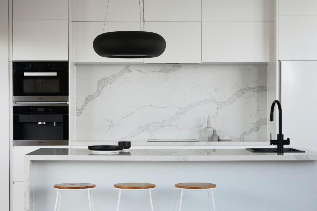 white kitchen with white marble backsplash and black fixtures