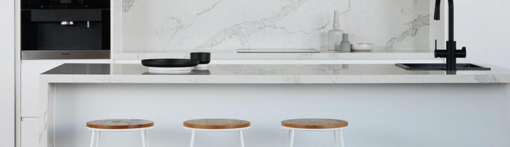 white kitchen with white marble backsplash and wooden stools