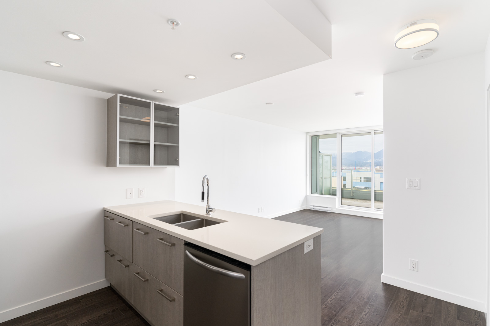 kitchen and living room floor to ceiling windows with a city view in the heatley at strathcona village