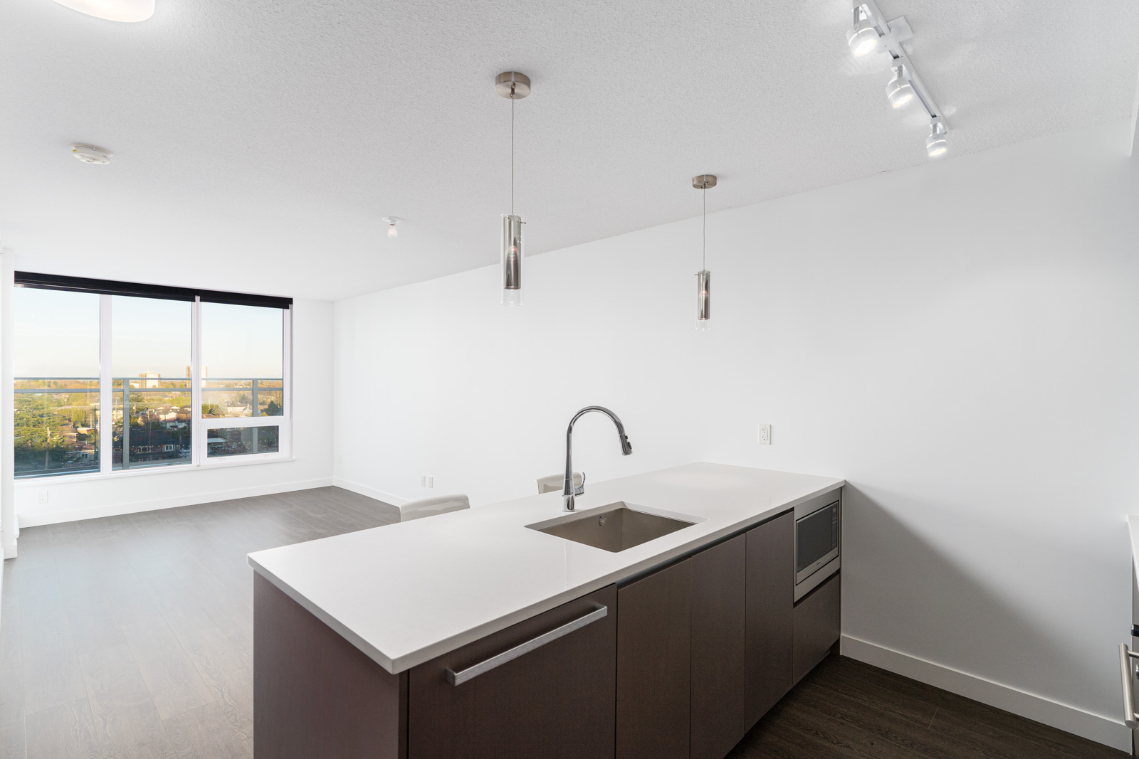 living room and kitchen with white walls and laminate flooring with a floor to ceiling windows in Richmond
