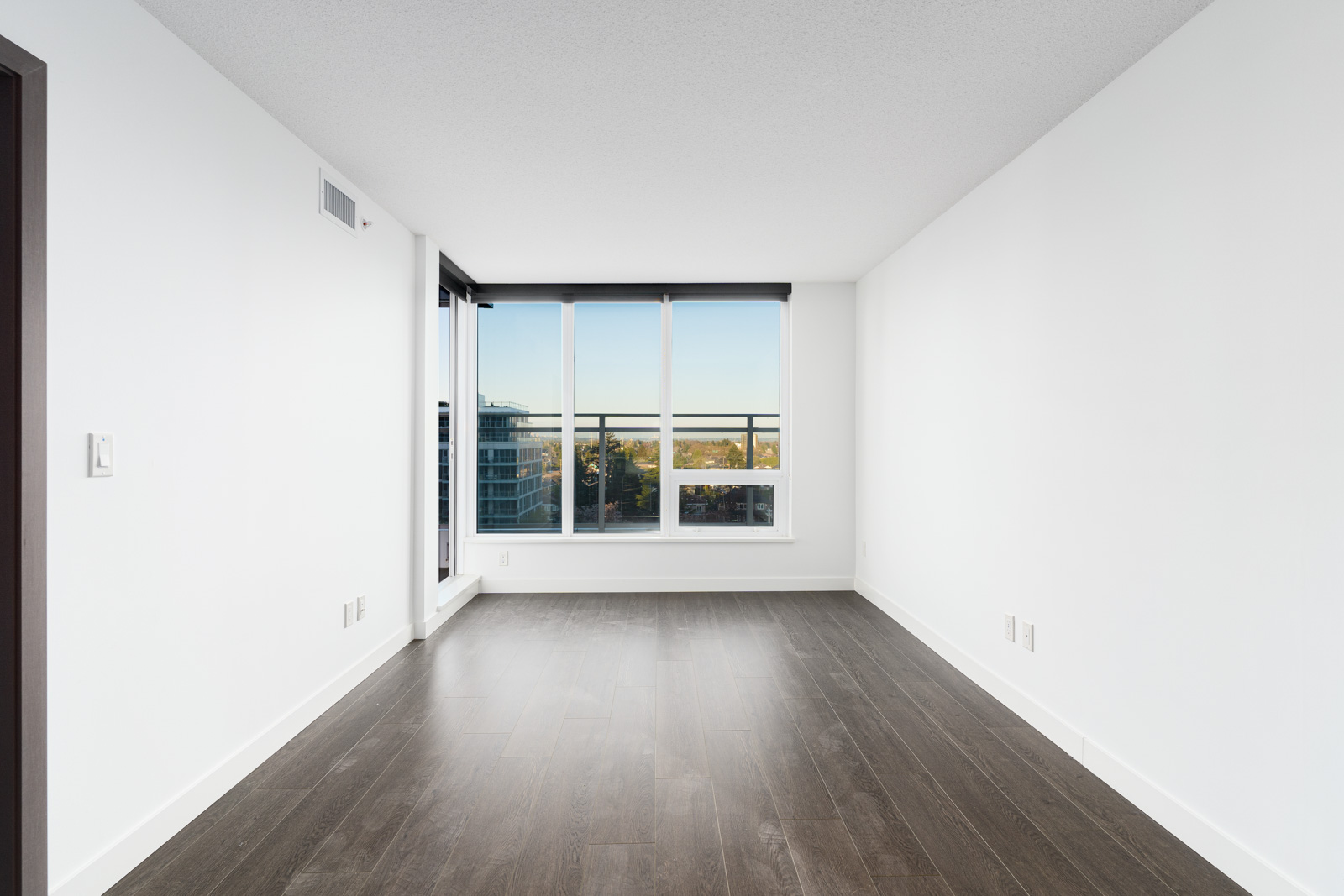 bright living room with laminate floors, white walls and floor to ceiling windows