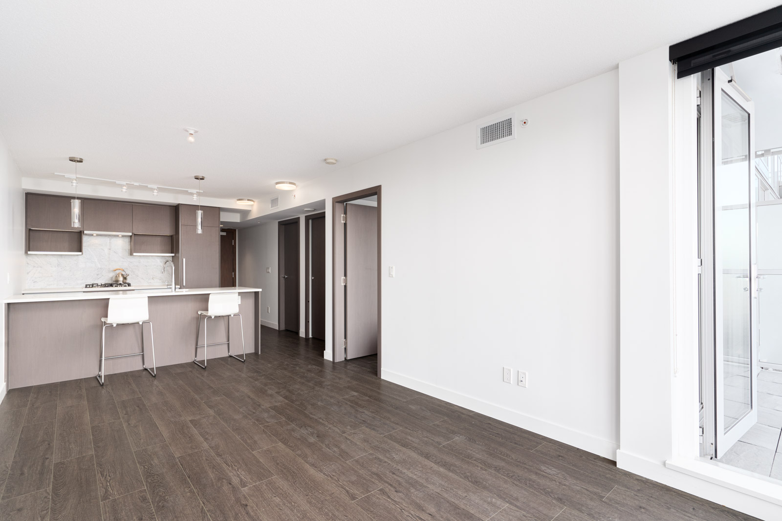 living room and kitchen area with laminate floors and white walls in a rental condo in richmond by birds nest properties