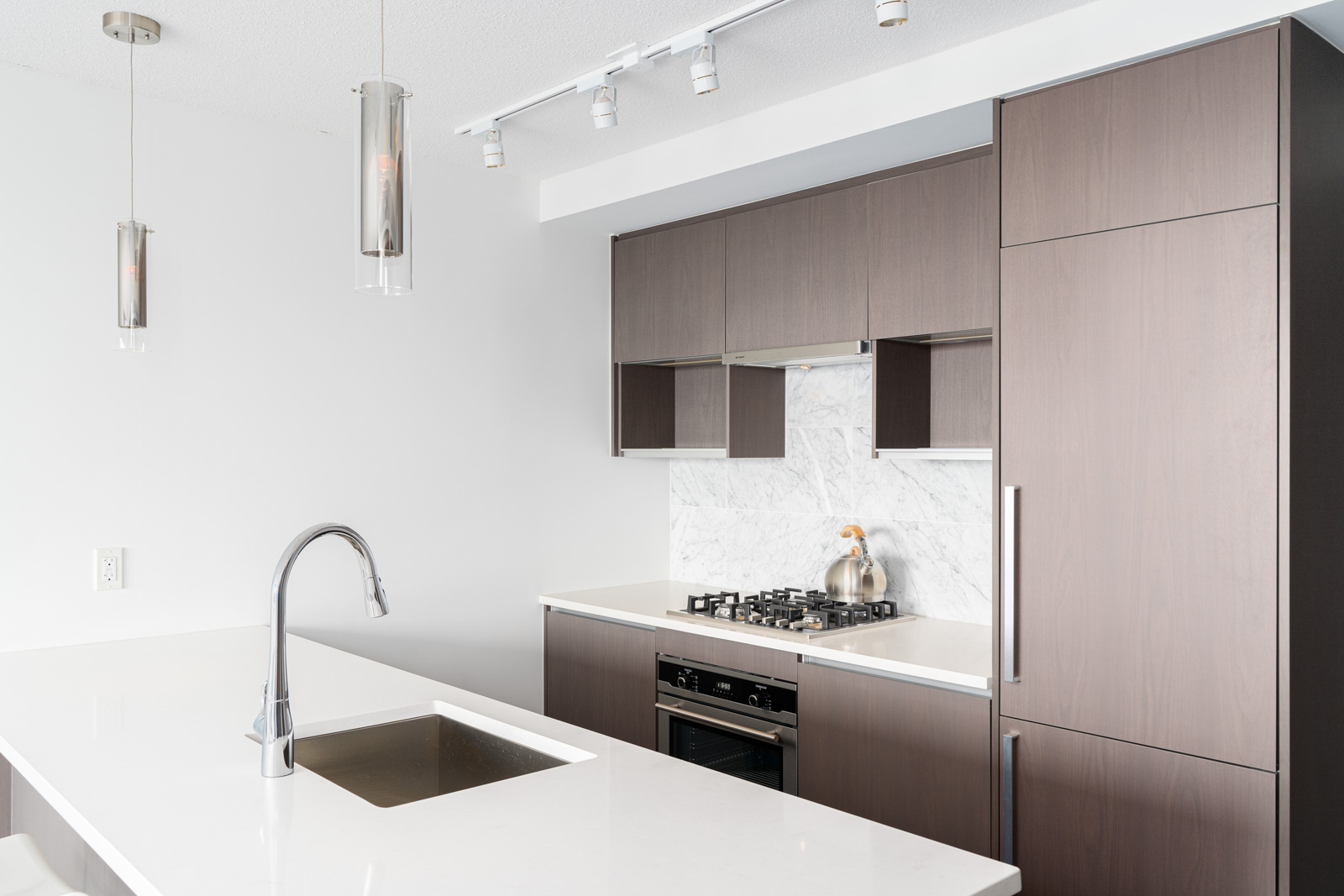 kitchen with stainless steel appliances and brown cabinets in a rental condo in richmond
