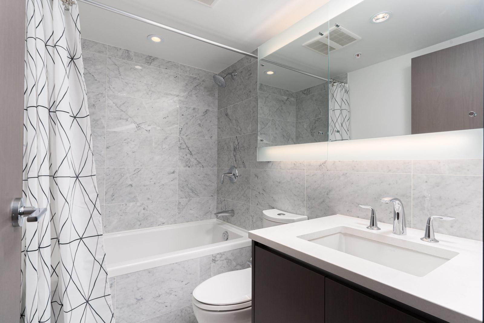 washroom with white sink and a bath tub in a rental condo in richmond