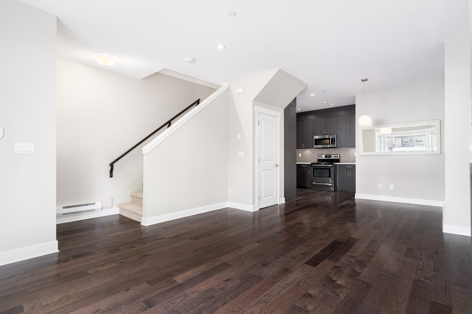 Open living area showing staircase and kitchen entry, with dark hardwood floors