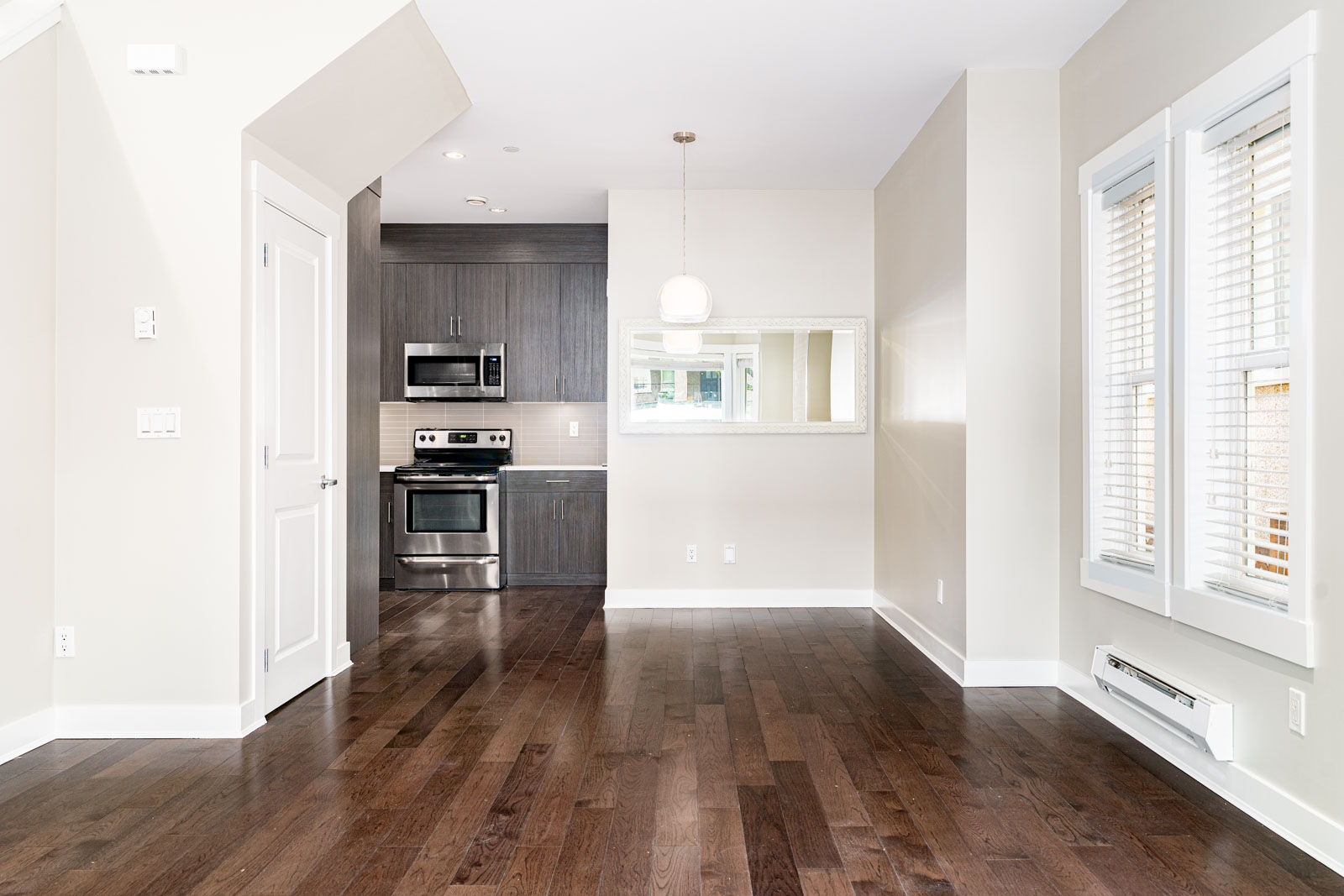 Open living area with dark hardwood floors and pale walls, showing kitchen entry and storage