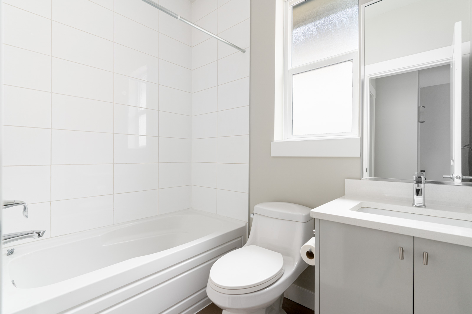 White/grey bathroom with bathtub / shower combination and toilet