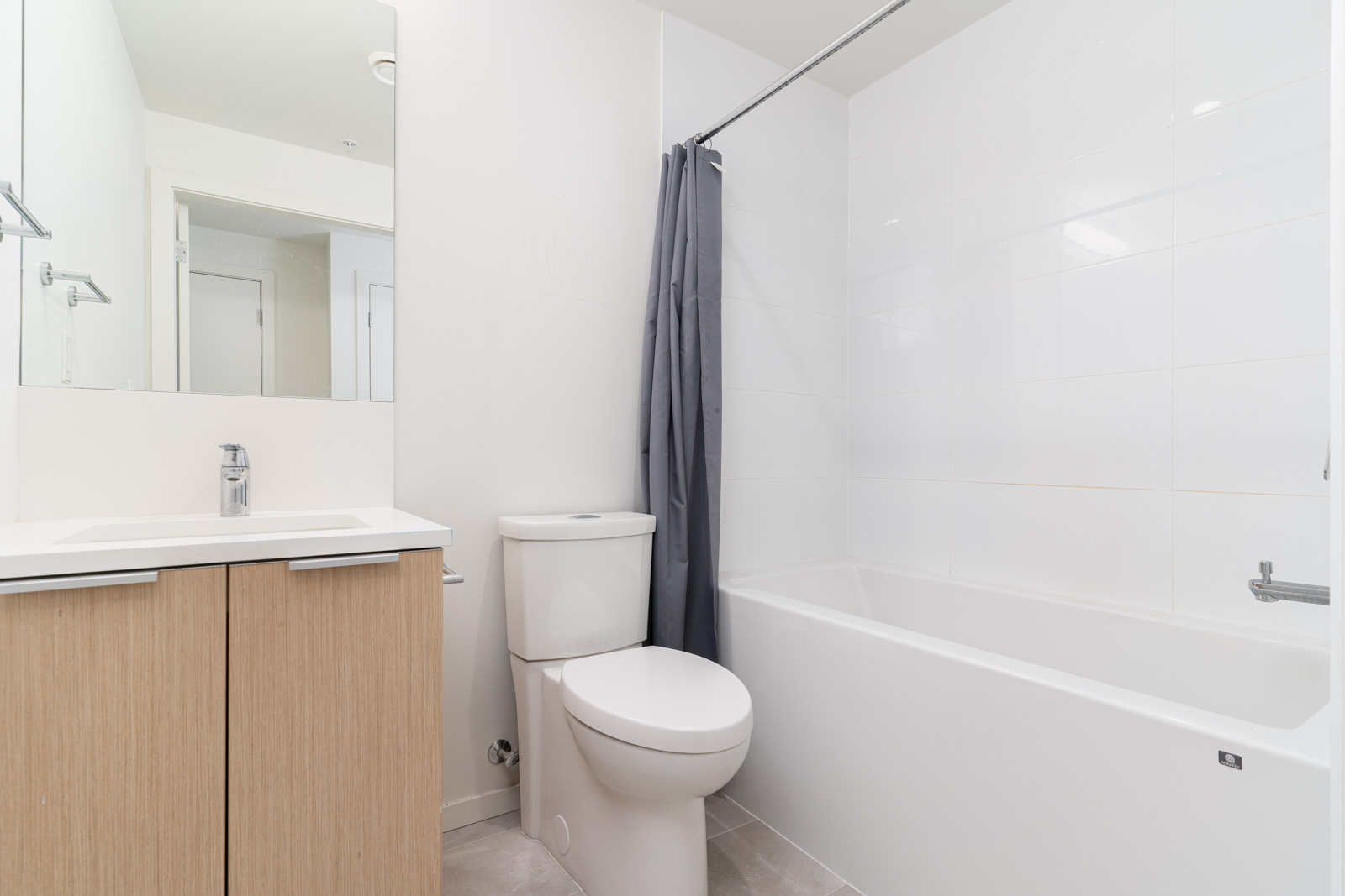 Washroom with bathtub/shower combo, toilet, modern vanity and single sink
