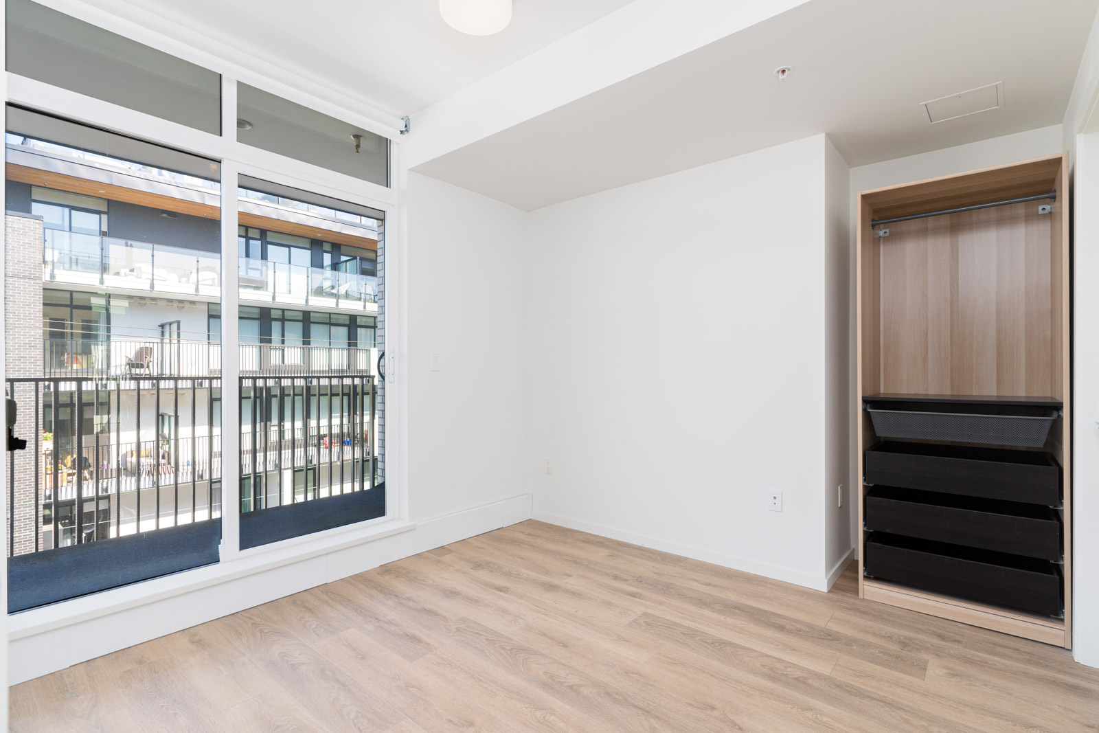 bedroom with large windows, balcony and open wardrobe with laminate floors