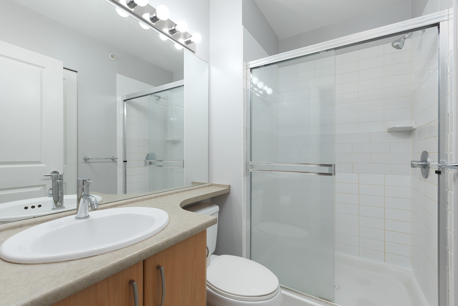 washroom with mirror and white walls with shower