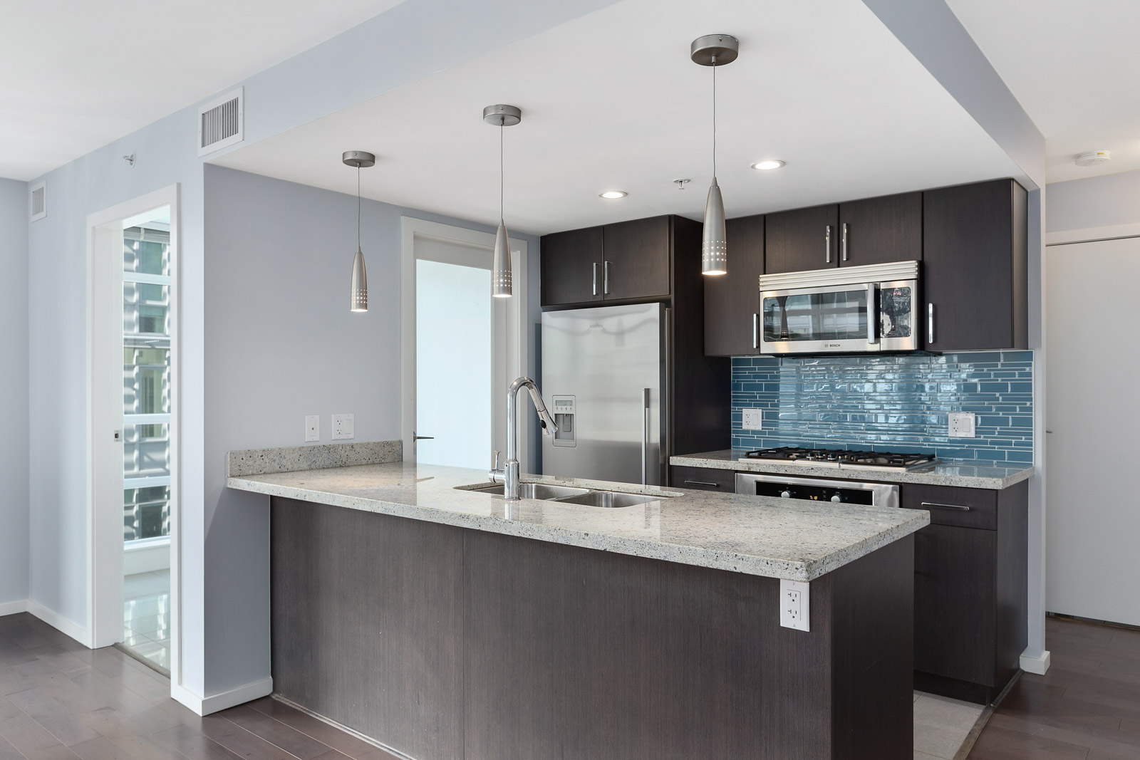 full kitchen with high end appliances in luxury condo located in olympic village