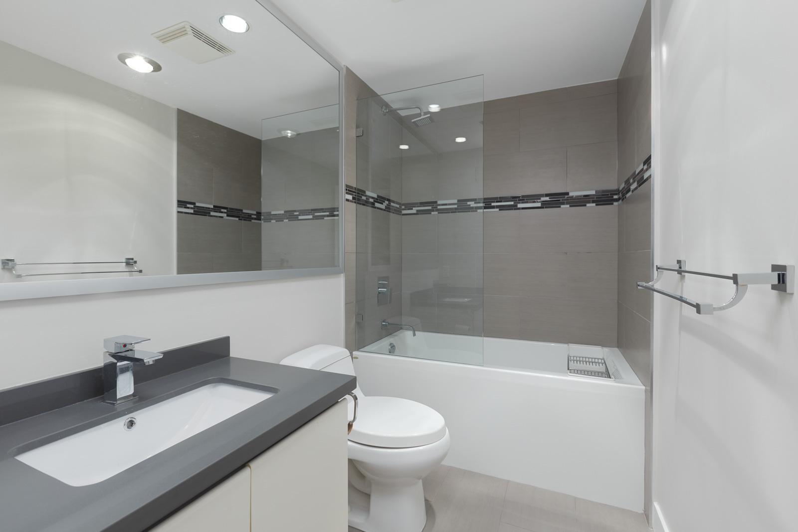 bathroom with big windows and white tub
