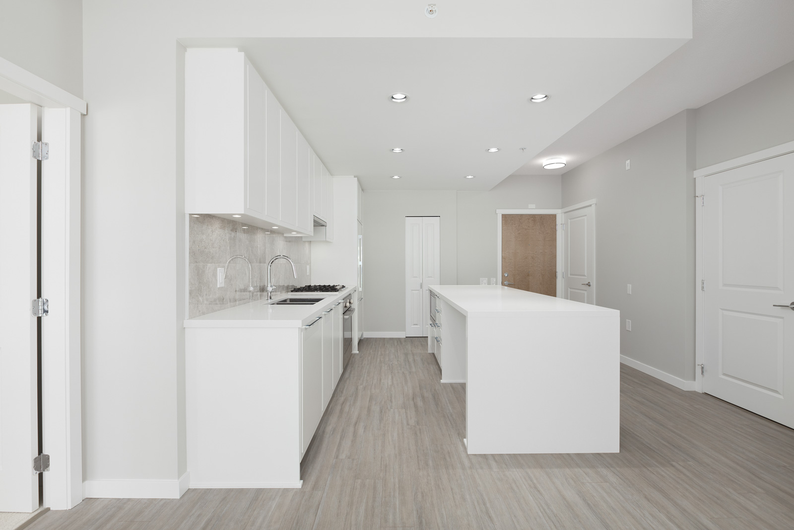 modern kitchen layout with island in luxury condo managed by Birds Nest Properties