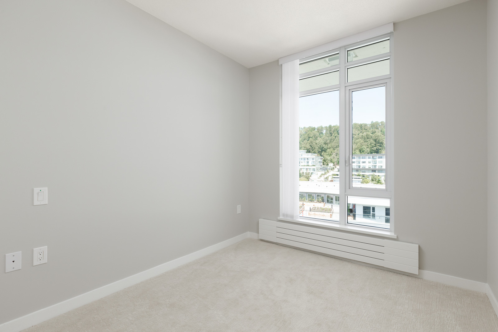 bedroom with white walls and window in rental condo in the River District neighbourhood of Vancouver