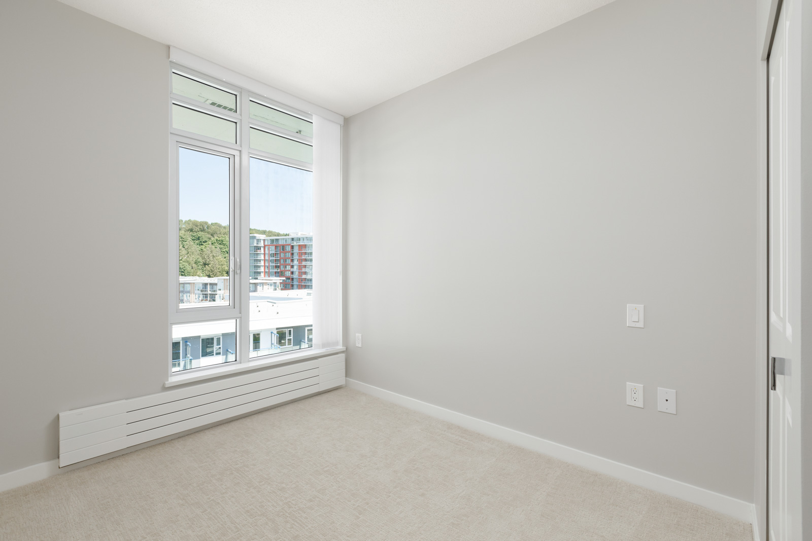 second bedroom with white walls and window in rental condo in the River District neighbourhood of Vancouver