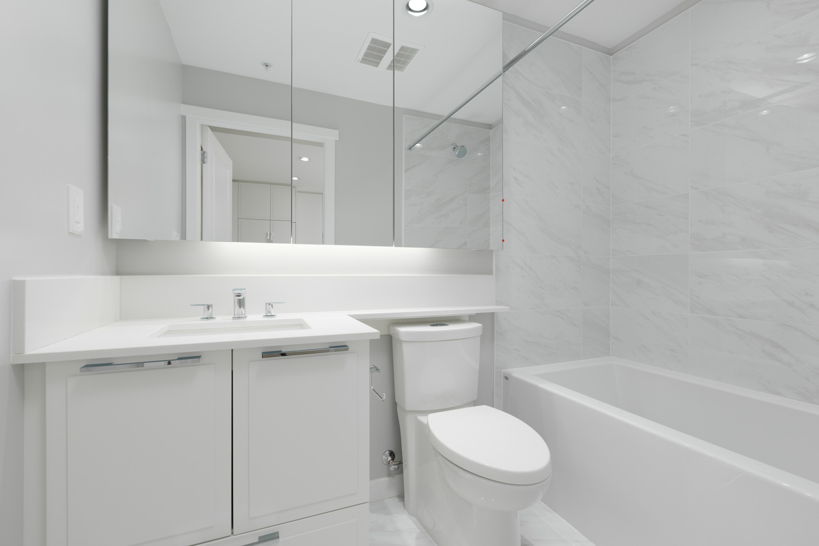 bathroom with white walls and tub and mirror