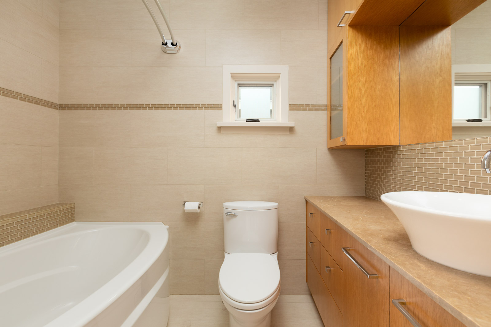 bathroom with tub and large mirror