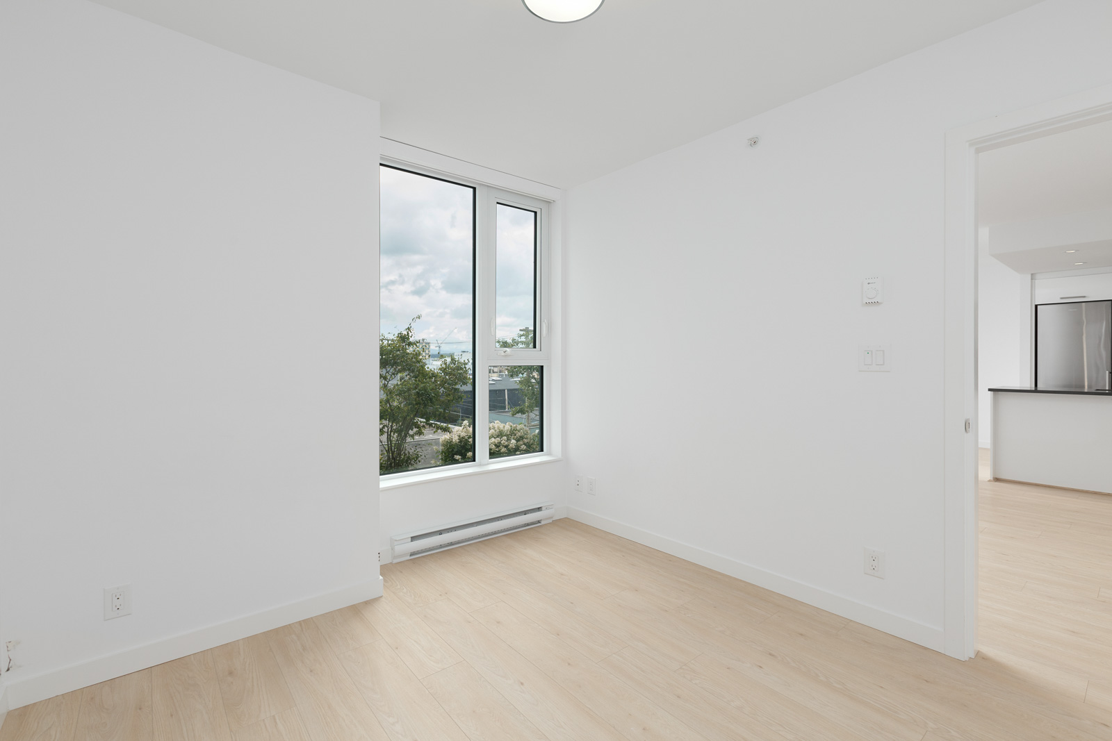 bedroom with laminated flooring and large windows