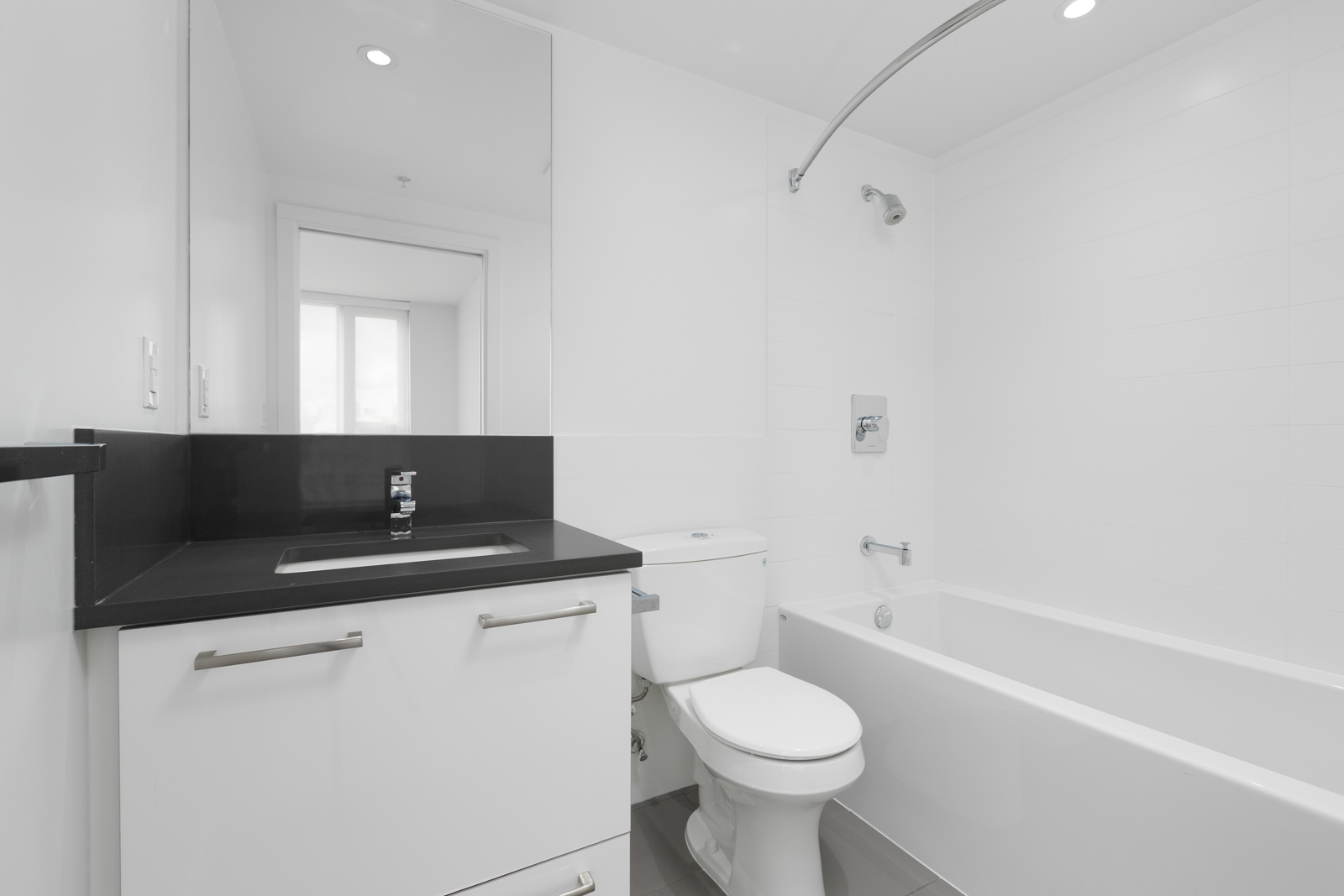 bathroom with white tub and huge mirror
