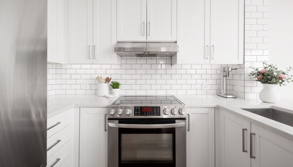 Yaeltown rental condo with white kitchen and fresh pink flowers