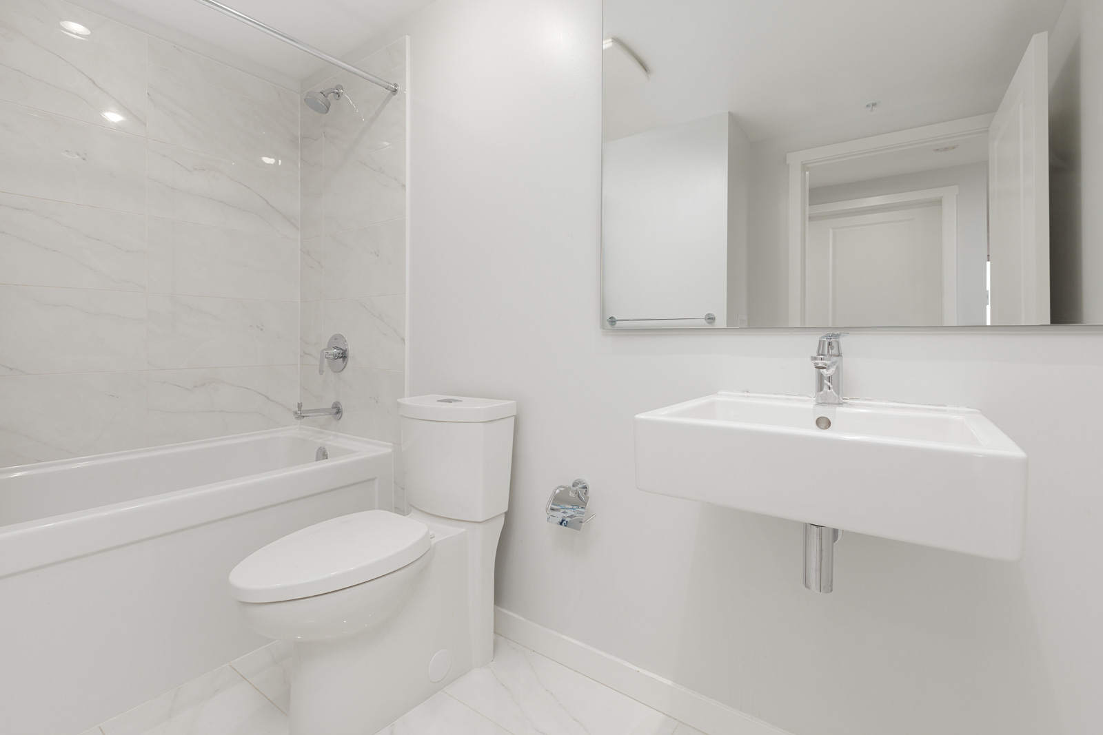 bathroom with toilet, sink, and tub
