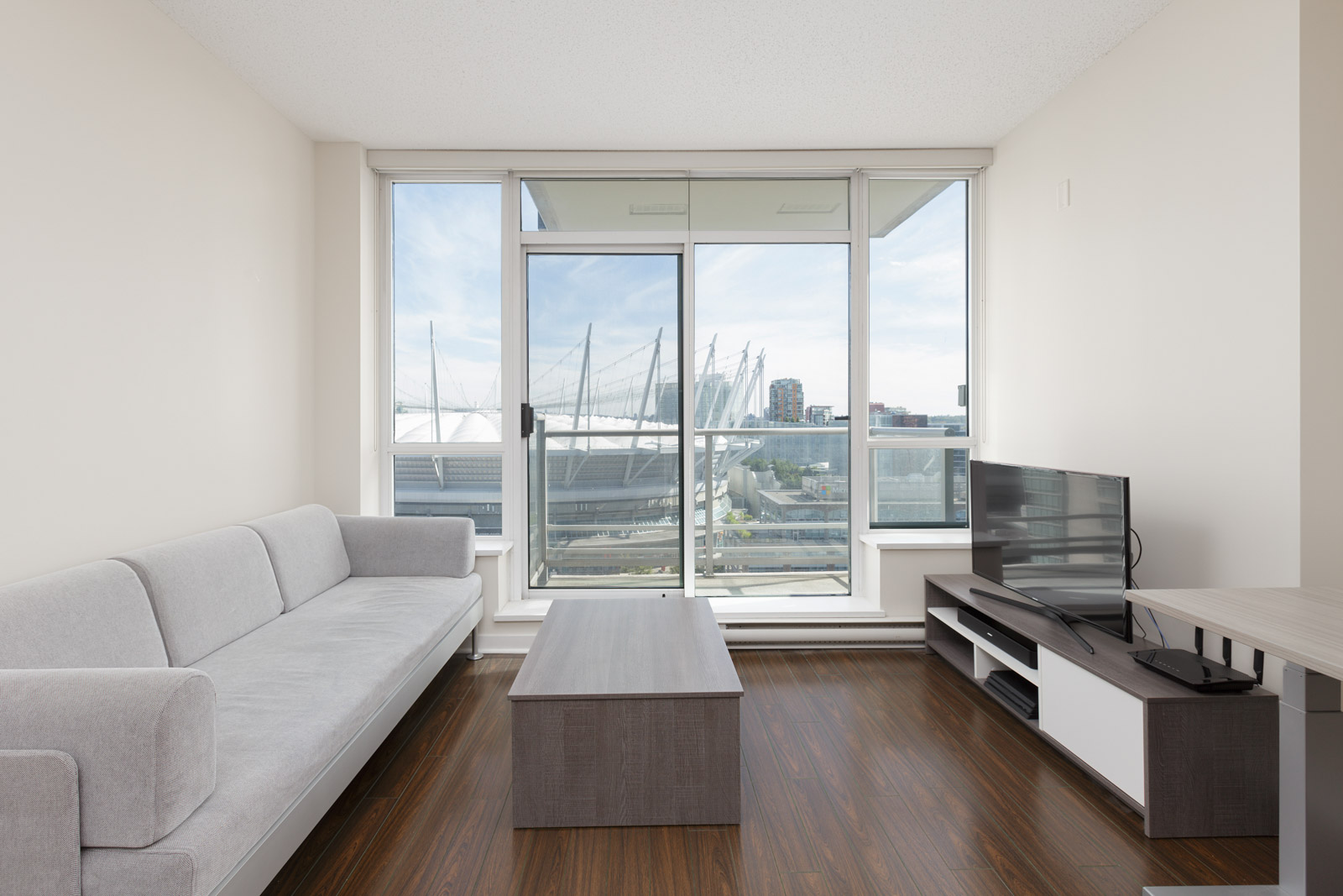 Living room inside upscale Yaletown condo with view of BC place in downtown Vancouver