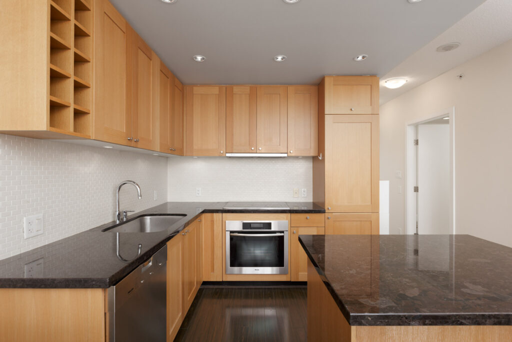 Kitchen inside upscale Yaletown condo with stone countertops