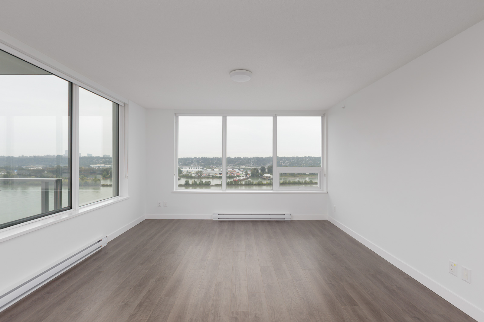 new clean living room with big windows and laminate floors